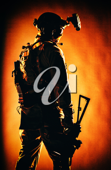 Army special forces soldier in tactical ammunition, night vision device on helmet, standing with lowered service rifle in hand low key, back view, studio shoot with red backlight on fabric background