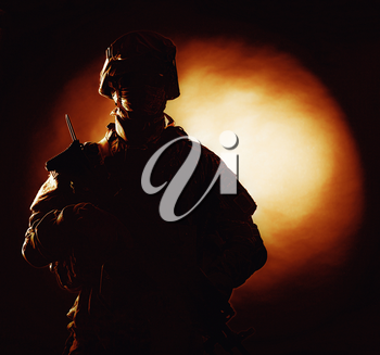 Silhouette photo of army soldier, modern combatant, military conflict participant standing in combat uniform with fiery spot on black background. Fire of war, ashes of battle, nuclear fire concept