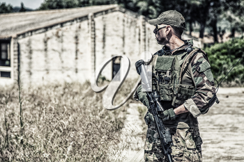 Navy SEALs fighter in ballistic goggles, equipped military ammunition and body armour, holding service rifle, looking in camera while standing outdoors. Special forces soldier half-length portrait