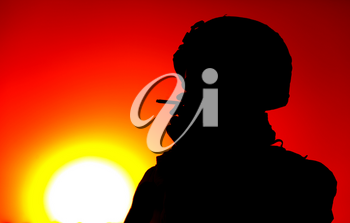 Silhouette of army soldier in combat helmet smoking cigarette on background of red sunset sky and setting sun backlight. Special operations forces fighter resting at end of day, relaxing after fight