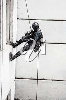 Spec ops police officer SWAT during rope exercises with weapons