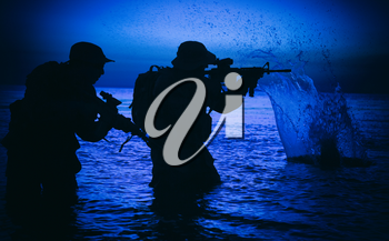 Army soldiers team, special operation forces infantrymen landing on seacoast, aiming and shooting with service rifle during firefight on shore at evening or morning time. Military amphibious operation