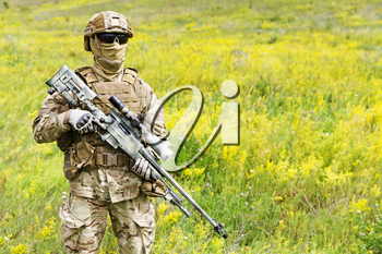 Equipped and armed special forces soldier in the blooming field with copy space for text