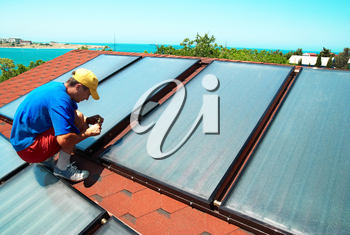 Worker mounting solar water heating panels on the roof.