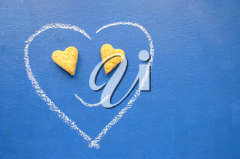 Valentine's Day card. Design by flyer, banner, poster, printing, mailing, postcard. Hand drawn smiley Heart shape on a blue background with heart shaped cookies.