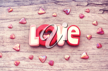 Word love with heart on wooden background