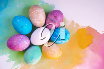 Watercolor background with colorful rainbow Easter eggs.
