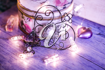 Vintage metal heart with a crystal on a background of violet drapery with lights of the garland. Mysterious Valentine's Day Concept.