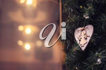 Wooden angel against the background of the festive window and decor of the branches of the Christmas tree. Greeting banner, postcard.