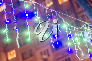 New year garlands on the blurred background of city houses.Urban Christmas photo.