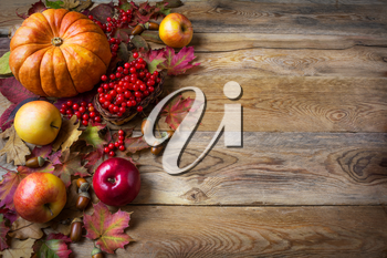 Thanksgiving  greeting background with pumpkins, apples and fall leaves. Thanksgiving background with seasonal vegetables and fruits.