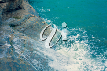 Bright Blue Ocean Surface with Waves and Foaming crashing againts the natural clay wall, Dark Turquoise Water Waving at the pace of the Breeze, Mediterranean Sea Landscape View from the Sky