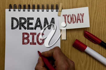 Conceptual hand writing showing Dream Big. Business photo text To think of something high value that you want to achieve Man holding marker notebook wooden table for today coffee cup