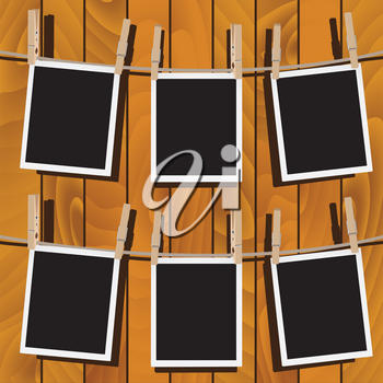 Retro photo frames hung on a rope with wooden clothespins.