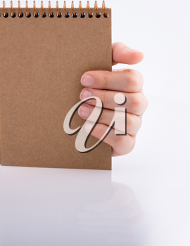 Hand holding brown color notebook  on a white background