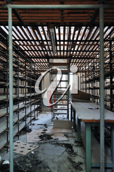 Empty shelves in abandoned vinyl records pressing factory storage room.