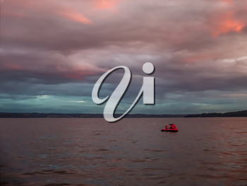 A jetski is anchored at Three Tree Point, Washington as the sun sets.  Pink and purple billowing clouds  blanket the Puget Soiund.