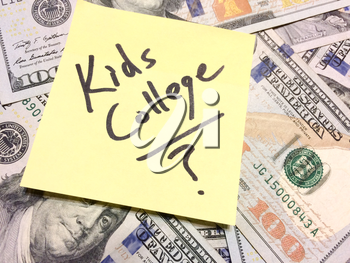 American cash money and yellow post it note with text Kids College with question mark in black color aerial view