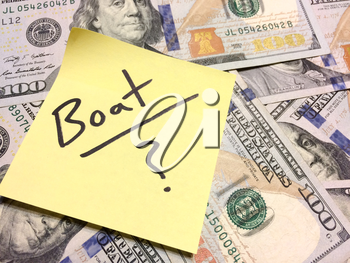 American cash money and yellow post it note with text Boat with question mark in black color aerial view