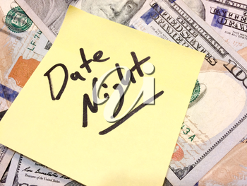 American cash money and yellow sticky note with text Date night in black color aerial view
