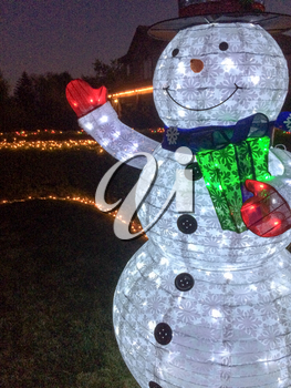snowman christmas decoration with lights in yard at night time