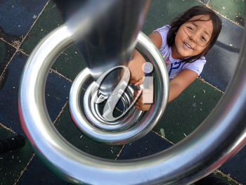 cute kid girl smiling at playground climbing up ladder spiral