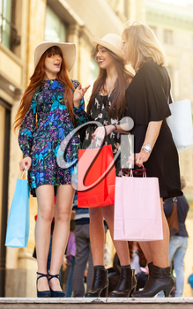 Three friends or mum with daughters go shopping.