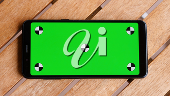 Top view smart phone place on table wood with green screen, Close-up the cell phone is on the brown desktop with chroma key and markers.