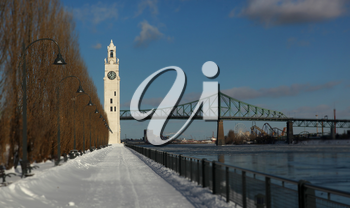Clock tower and Jacques Cartier bridge during winter in the old port, Montreal
