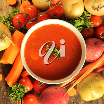 Vegetables soup surrounded by fresh vegetables and a spoon on a wooden background