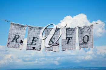 Letters resto write on a teatowel and hang on a clothesline in a blue sky